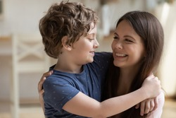 Close up of happy young mother hold in arms look in eyes cuddle cute little son, smiling mom hug embrace small preschooler boy child enjoying weekend spending leisure family time together