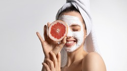 Close up of happy young playful teen girl in moisturizing mask and towel holds grapefruit covers eye. Advertising poster of facial eco-friendly skincare products. Morning beauty routine
