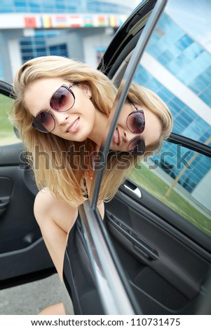 Close-up of happy young pretty woman looking at camera and sitting her car
