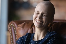 Close up of happy young sick woman suffering from cancer laugh smile feel positive optimistic about future recovery, overjoyed millennial ill female patient with oncology show high spirit optimism