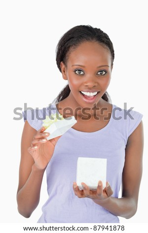 Close up of happy young woman opening a present against a white background