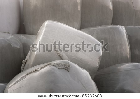 Close up of hay bales wrapped in plastic - stock photo