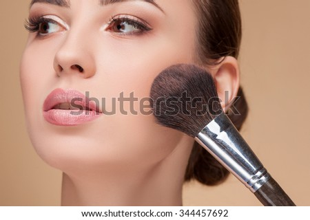 Close up of head of cheerful girl attending beauty shop. The visagiste is applying powder on female check with a brush. The lady is looking forward with serenity #344457692