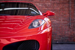 Close up of headlight detail of modern luxury sportscar with reflection on red paint after wash & wax. Front view of supercar with brick wall. Concept of car detailing and paint protection background.