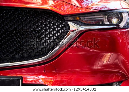 Close-up of headlights, grill and hood of a red modern car. Details of a luxury car.