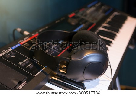 Close up of headphone on keyboard in music studio room, music instrument concept