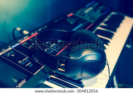 Close up of headphone on keyboard in music studio room, music instrument concept, blue color tone
