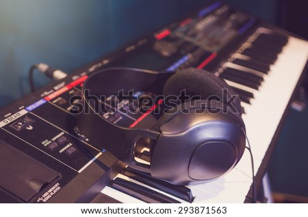 Close up of headphone on keyboard in music studio room, music instrument concept, vintage pastel tone