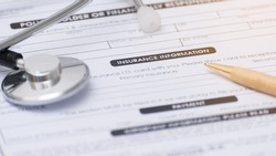 Close-up of health insurance form,Stethoscope and pen on a health insurance application medical information