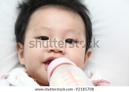 Close up of healthy baby about 6 months drinking milk from nursing bottle