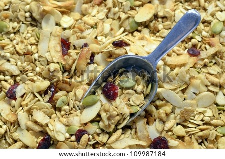 Close up of healthy organic dried fruit and nut granola with a metal scoop