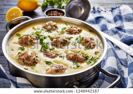 close-up of hearty Greek Meatball Soup - Giouvarlakia, Youvarlakia in Egg lemon sauce in a metal casserole on a wooden table with kitchen towel and ladle, view from above