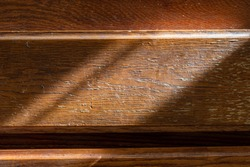 Close up of heavily weathered wood texture. The golden wood features many different patterns and striations  along its grain.