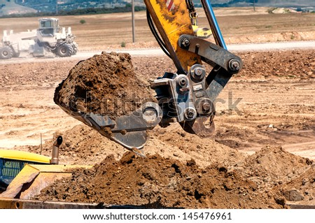 Close-up of heavy duty excavator scooping into earth and loading a dumper truck