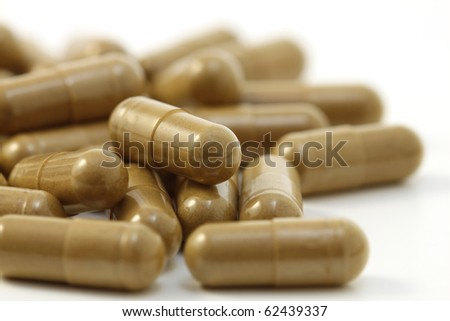 Close-up of herbs capsules. Isolated on white background.