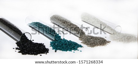 Close-up of high density polyethylene (HDPE) granules in glass capsule, black granule, white granule,