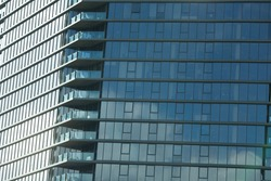 Close up of high rise apartment building in Melbourne's CBD with mirror window reflections. City living in small crowded skyscraper units and flats. Housing options or business offices CBD development