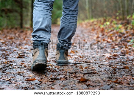 Close up of hiker walking down the wet forest path. Person with dirty hiking shoes on the footpath outdoors. Photo stock ©