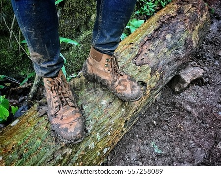 Close up of hiking boots and legs climbing up rocky trail, dirty boots