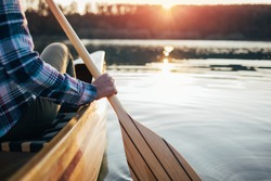 Close up of hipster girl holding canoe paddle. Canoeing on the sunset lake