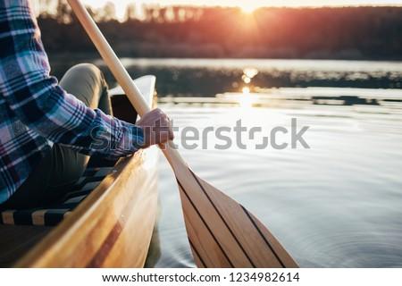 Close up of hipster girl holding canoe paddle. Canoeing on the sunset lake