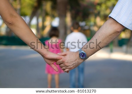 Close up of holding hands, two kids in background