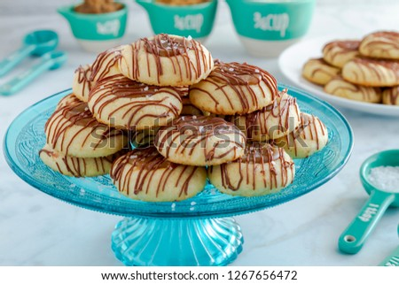 Close up of holiday salted caramel thumbprint cookies drizzled with milk chocolate sitting on blue glass pastry stand and additional cookies on plate surrounded by ingredients in blue utensils
