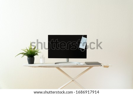 Close up of home office workspace during coronavirus quarantine, a desktop computer placed on ironing board with face mask hanging on it, hand sanitiser, mouse, keyboard and a plant Photo stock ©