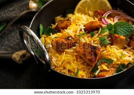 Close up of Homemade Chicken Tikka Biryani served with Raita on dark moody background, selective focus