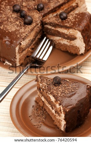 Close-up of homemade chocolate cake and fork on beige mat.