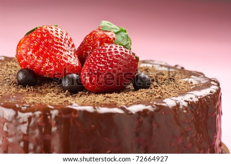 Close-up of homemade chocolate cake with strawberries on pink background.