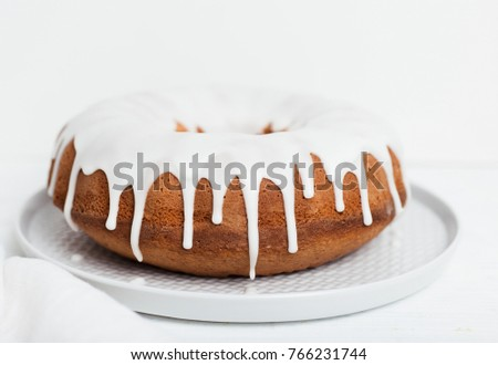 Close-up of homemade lemon bundt cake with thick, drizzling vanilla icing on light grey plate with cloth napkin on white wooden table