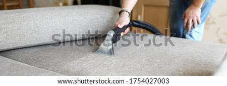 Close-up of hoover for furniture and dirty sofa. Hoovering and cleaning house, housekeeper or special service for house cleanliness maintenance. Washing fabric cloth
