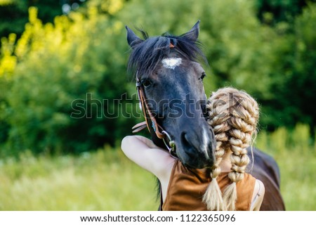 Close up of horse and young blonde woman with two braids hugging. People and animals friendship concept. - Shutterstock ID 1122365096