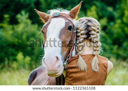 Close up of horse and young blonde woman with two braids hugging. People and animals friendship concept.
