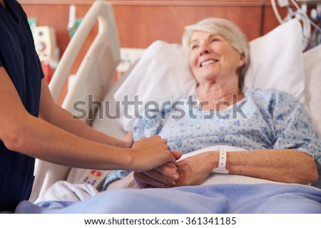 Close Up Of Hospital Nurse Holding Senior Patient\'s Hand