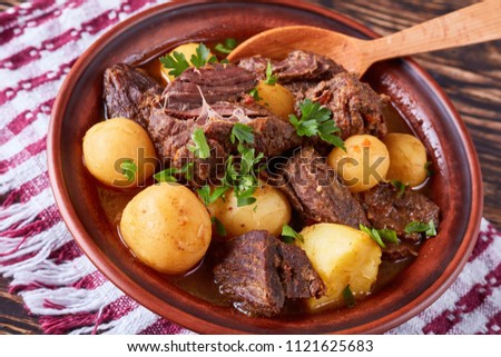 close-up of hot Beef Stew with tender cubes of meat, whole new potatoes, onion and herbs in a clay bowl on old rustic wooden table with napkin, irish cuisine, horizontal view from above