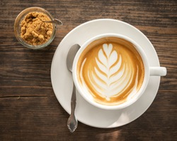 Close up of hot cappuccino coffee with beautiful latte art in a white ceramic cup on a wooden table background with brown sugar in a small glass. Top view.