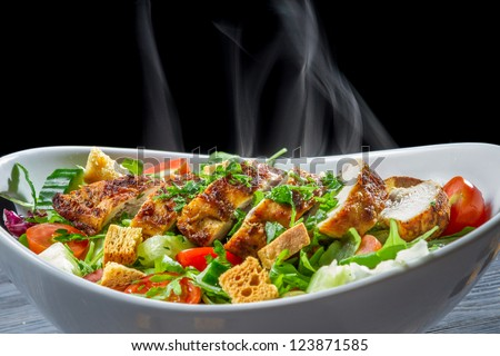 Close-up of hot chicken Caesar salad with vegetables