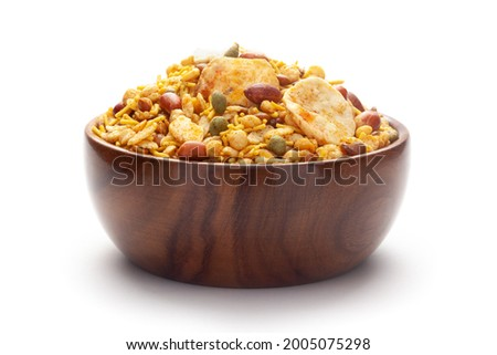 Close-Up of Hot spicy Nav Ratan snacks In hand-made (handcrafted) wooden bowl, made with red chili, peanuts. Indian spicy snacks (Namkeen), Imagine de stoc ©