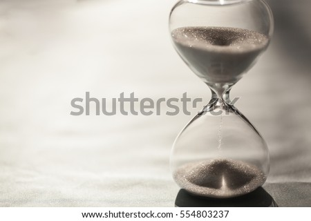 Close up of hourglass clock. Hourglass time passing concept for business deadline, urgency and running out of time #554803237