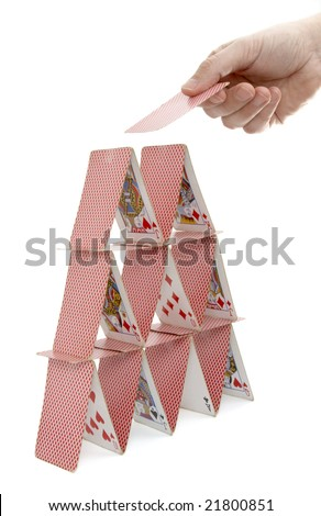 close up of house of playing cards and hand on white background with clipping path