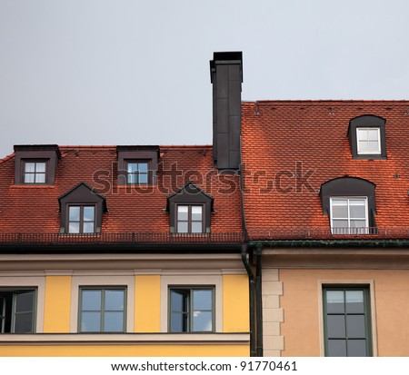 Close-up of  houses with red tile roof, chimney, attic, windows and downspout in Munich, Germany