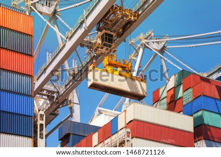 Close-up of how containers are being discharged from a large container ship by a crane in the port of Rotterdam, Europe