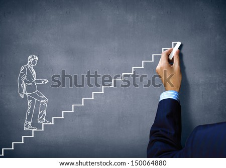 Close up of human hand drawing career ladder with chalk