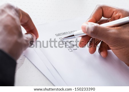 Close-up Of Human Hand Filling Customer Survey Form