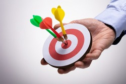 Close-up Of Human Hand Holding Colorful Darts On Target Against Background