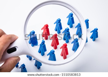 Close-up Of Human Hand Holding Magnifying Glass Over Red And Blue Human Figures