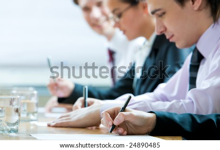 Close-up of human hand holding pen over paper on background of working people