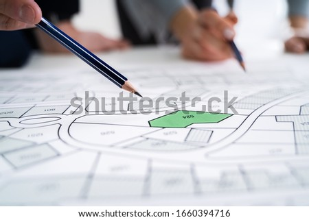 Close-up Of Human Hand Holding Pencil Over Paper Cadastre Map Foto stock ©